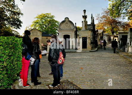 Paris, France - 'Pere Lachaise' Cemetery, Female Teens Asking Passerby for Directions Grave Site, group - Stock Image