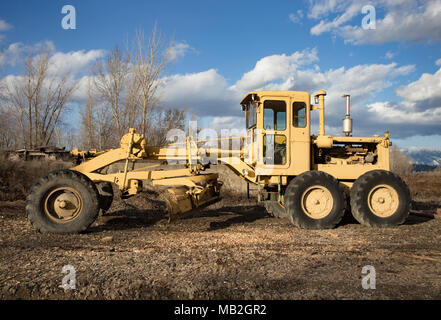 A yellow Caterpillar motor grader, on the yard, at Fodge Pulp Products, in Bonners Ferry, Idaho, USA.   Fodge Pulp Products is a pulp wood processing  - Stock Image