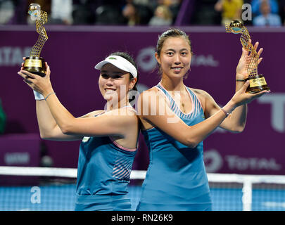 Doha, Qatar. 16th Feb, 2019. Hao-Ching Chan (R) and Latisha Chan of Chinese Taipei hold up the trophy during the awarding ceremony after the doubles final against Demi Schuurs of the Nederlands and Anna-Lena Groenefeld of Germany at the 2019 WTA Qatar Open in Doha, Qatar, Feb. 16, 2019. Credit: Nikku/Xinhua/Alamy Live News - Stock Image