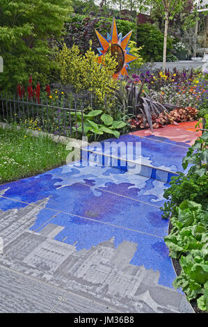 A contemporary garden dsign with colourful borders and mosaic decoration - Stock Image