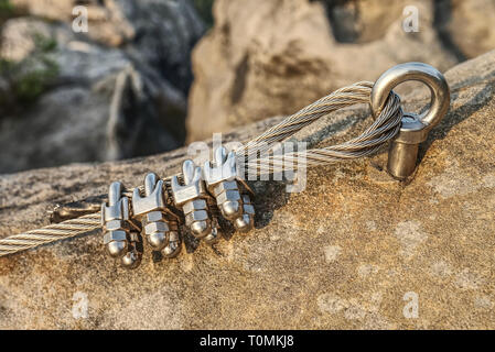 Mountain iron anchor for free climbing. Stainless cable fixed to the rock for the safety of the walking route in the mountains - Stock Image