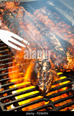 BBQ Ribs on a barbecue grill with flames and a meat fork - Stock Image