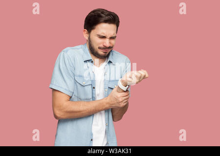 Hand pain. Portrait of sick handsome bearded young man in blue casual style shirt standing and holding his painful hands. indoor studio shot, isolated - Stock Image