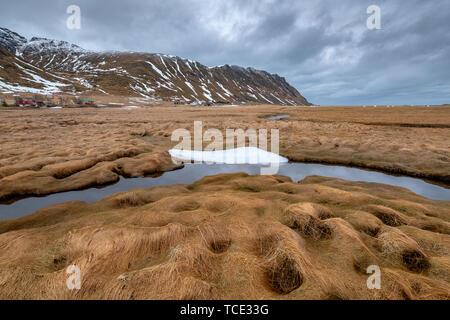 Fredvang village at the foot of the mountains, Moskenesoya, Flakstad, Lofoten, Nordland, Norway - Stock Image