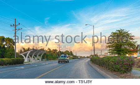 Motion blur of old American car driving with a beautiful split color sky typical of the sunset hours. Wide angle view - Stock Image