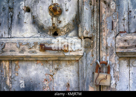 Sicily - old distressed door with locks and flaking paint. - Stock Image