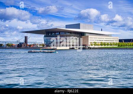 23 September 2018: Copenhagen, Denmark - The Copenhagen Opera House, or Operaen, on Holmen Island, with a tourist boat passing on the harbour. - Stock Image