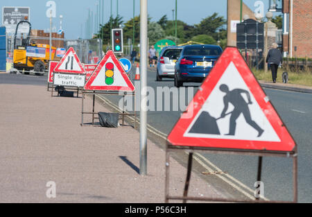 Temporary traffic lights at roadworks on a road in the UK. - Stock Image