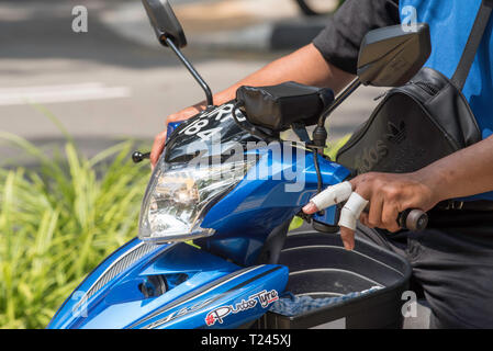 The top front part of a motor scooter and rider with bandaged injured fingers riding in Singapore traffic - Stock Image