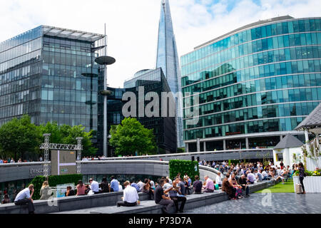 Office workers enjoy lunch time outdoors near London's Tower Bridge on another very hot day. The present heatwave is set to continue. ©Tim Ring/Alamy Live News - Stock Image