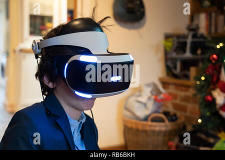 An 8 year old boy wearing a Sony Virtual Reality headset and playing a virtual reality computer game - Stock Image