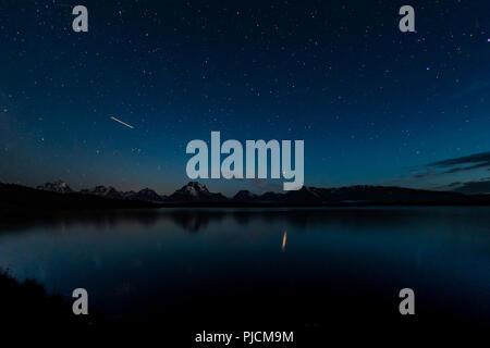 Airplane Light and Stars over Jackson Lake and Grand Teton Range - Stock Image