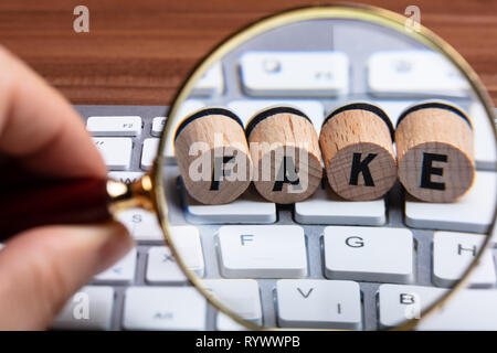 Man's Hand Holding Magnifying Glass Over Wooden Cork With Fake Text On White Keyboard - Stock Image