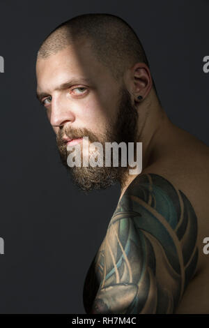 Portrait serious man with beard and tattooed shoulder - Stock Image