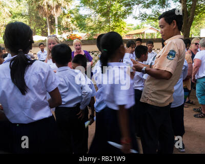 Cambodian school children surrounding tourists who are handing out gifts of soap shampoo toothbrushes and combs collected from hotels during tour - Stock Image