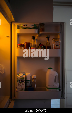 An open door of a fridge with a few dairy items and other refrigerated food. - Stock Image
