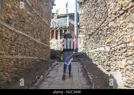 Young Pretty Woman Wearing Red Jacket Backpack Crossing Mountains Village.Mountain Trekking Rocks Path.Old Town - Stock Image