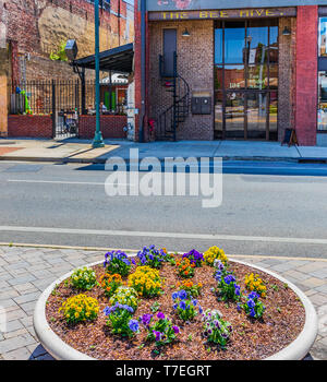 JOHNSON CITY, TN, USA-4/27/19: A large, colorful flowerpot sets across the street from an outdoor restaurant on East Market Street. - Stock Image