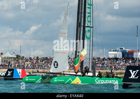 Portsmouth, UK. 25th July 2015.  Groupama Team France cross the line at the end of the first race close to the watching - Stock Image