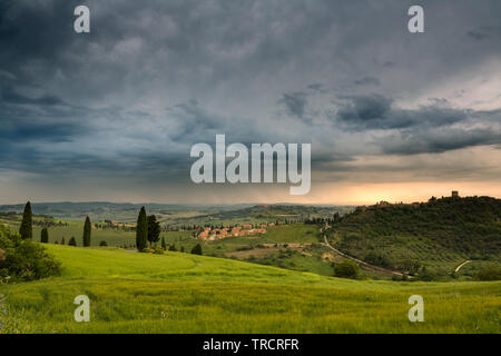 Walls and towers of the town of Monticchiello in Tuscany Italy during a rainstorm at sunset - Stock Image