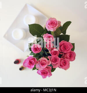 A Bunch of pink flowers in a vase. The photo is taken from above (flatlay). In addition to roses there is white candles and two nail polishes. - Stock Image