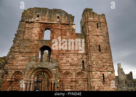 Front of Lindisfarne church and monastery ruins of the medieval priory with cross arrow loops on Holy Island of Lindisfarne England UK - Stock Image