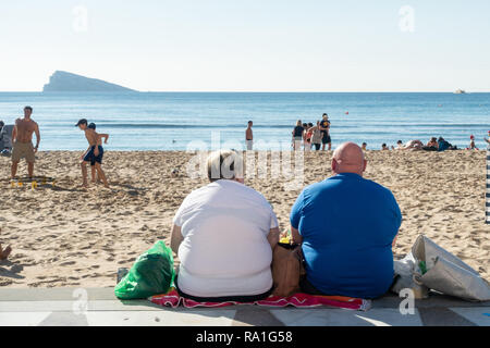 Benidorm, Spain. 30 December 2018. British tourists mix with locals on the beaches and in the bars and restaurants as they escape the cold British weather and head south to Spain. High temperatures meant that the beaches were busy from early morning with families enjoying the calm sea and temps of about 17 Celsius. Obese man and woman sitting facing the sea in this popular Spanish resort. Credit: Mick Flynn/Alamy Live News - Stock Image