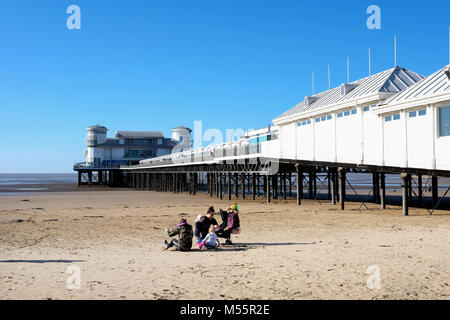 Weston Super Mare, UK. 20th February, 2018. A young family make the most of some rare winter sunshine, and blue - Stock Image