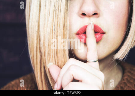 Close up of a beautiful blonde woman doing a silent gesture - Stock Image