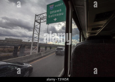 MONTREAL, CANADA - NOVEMBER 10, 2018: Roadsign indicating the direction of Ottawa  (Ontario) & Gatineau from the large window of a coach on a Quebec h - Stock Image