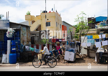 Poverty in Chennai, India, where a man cycles in front of run down houses and rubbish - Stock Image