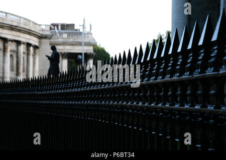 Black painted steel railing leading the eye towards an old city building with statue in the gardens, Dublin, Ireland. - Stock Image