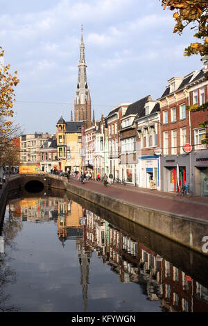 Old canal at Voorstreek in central Leeuwarden, The Netherlands, with iconic 19th century tower of the church of - Stock Image