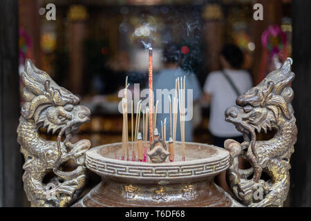 Burning incense in an incense burner with two lions at a Land God temple in Taipei, Taiwan. - Stock Image