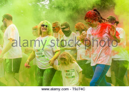 Kendal, Cumbria, UK, 19 May 2019. Participants get covered in powdered paint at the Kendal Colour Dash, a 5km fun run filled with colour with the accompaniment of a samba drumming band. The popular event, with 1200 participants, raises money for St Johns Hospice, a local independent charity providing care and support for patients and families living with life shortening conditions in North Lancashire and South Lakeland.   Credit Keith Douglas News/Alamy Live News - Stock Image