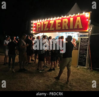 Pizzeria at festival at night with group of people, Silverstone Woodlands, Formula One, British Grand Prix, Northampton, England, UK - Stock Image