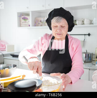 An old woman making pancakes in the bright kitchen. Making dough in the bowl - Stock Image