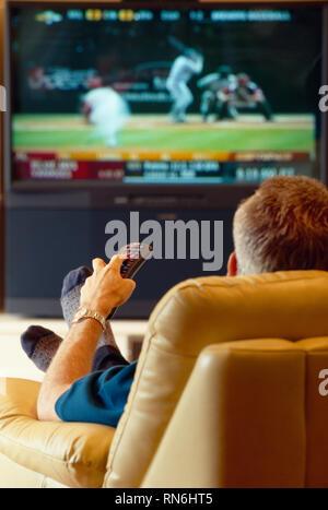 Mature man watching a baseball game on TV, USA - Stock Image