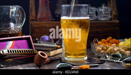 Pouring lager beer on a pint glass in a pub - Stock Image