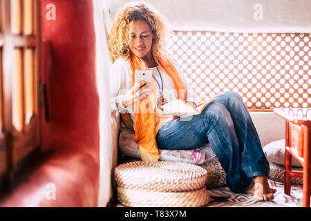 Fashion trendy attractive people young woman at home sitting and use mobile phone at home - hippy style clothes and coloured house - female and techno - Stock Image