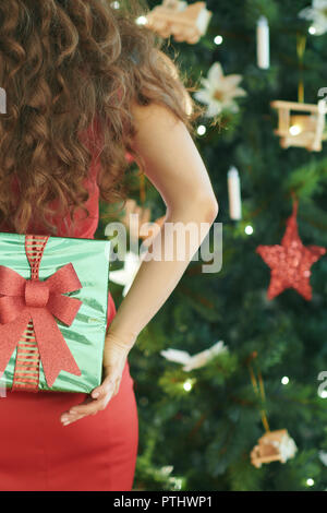 smiling modern woman in red dress near Christmas tree hiding green Christmas present box behind back - Stock Image