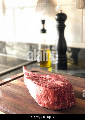 Close up of raw thick tomahawk ribeye beef steak on cutting board. Oil dispenser and pepper mill in the background. - Stock Image