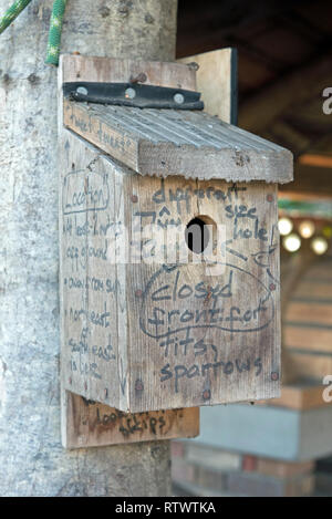 Wooden nestbox with advice for it's location and which species of birds are likely to use that type of box it written onto it. - Stock Image