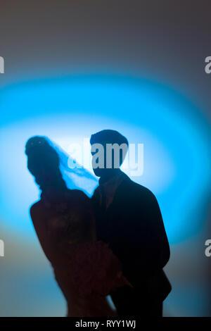 Wedding couple marriage cake topper plastic figures with tuxedo evening suit, white weddding dress veil. - Stock Image