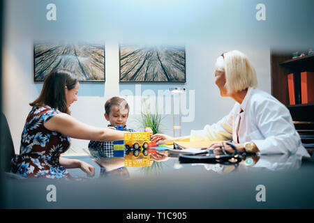Happy Doctor Woman Working And Playing With Mom And Boy - Stock Image