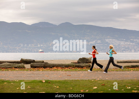 Two young women jogging along Spanish Bank Beach in Vancouver, British Columbia, Canada - Stock Image