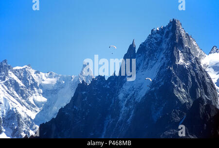 Parapentes flying in front of the Aiguille de Grepon and de la Republique in the French Alps, with the Dent de Geant and the Rochefort Arete beyond - Stock Image