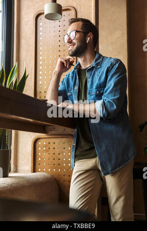 Photo of brunette confident man wearing glasses writing and using earpod with laptop while working in cafe indoors - Stock Image