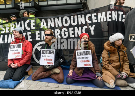 London, UK. 21st December 2018. Climate campaigners from Extinction Rebellion protest at the BBC meditating in front of the banner 'Public Service Announcement - Climate Emergency'. They call onthe BBC to stop ignoring the climate emergency & mass extinctions taking place and promoting destructive high-carbon living through programmes such as Top Gear and those on fashion, travel, makeovers etc. The protest, organised by the Climate Media Coalition (CMC) and its director Donnachadh McCarthy brought mannequins wrapped in white cloth to the BBC representing the bodies of a Greek village killed b - Stock Image