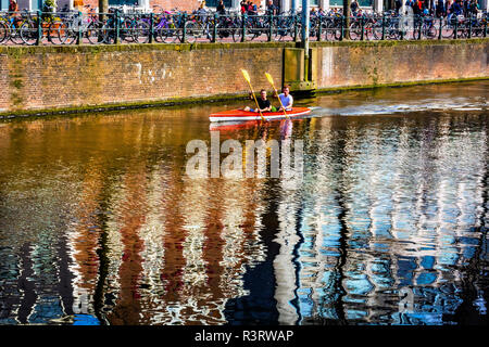 Kayak rowing reflection Singel Canal. Amsterdam, Holland, Netherlands. Canals in Amsterdam create beautiful abstract reflections. - Stock Image